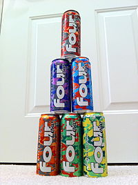 Six cans of four loko drinking beverage are arranged in pyramidal fashion.
